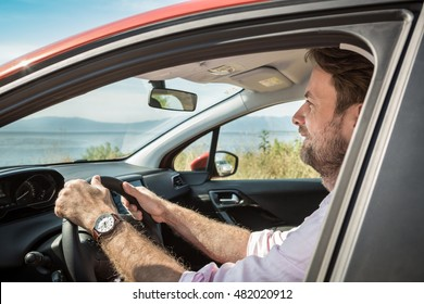 Happy smiling forty years old caucasian man driving a car. Sunny summer day and beautiful landscape (mountain, sea) as background.