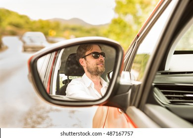 Happy smiling forty years old caucasian man (driver) reflected in a car wing mirror. Summer day and road in perspective as background.