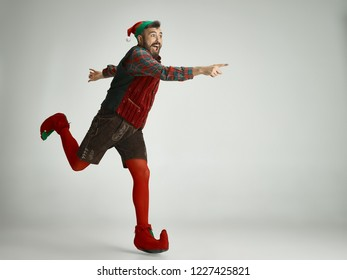 The happy smiling friendly man dressed like a funny gnome or elf posing on an isolated gray studio background. The winter, holiday, christmas concept