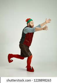 The happy smiling friendly man dressed like a funny gnome or elf running on an isolated gray studio background. The winter, holiday, christmas concept