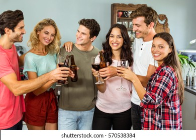 Happy smiling friends toasting drinks at home