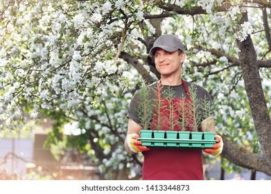 Happy smiling gardener loking to his blooking garden