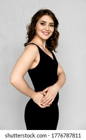Happy smiling girl in black dress with lace hem and stripes holds both hands on waist