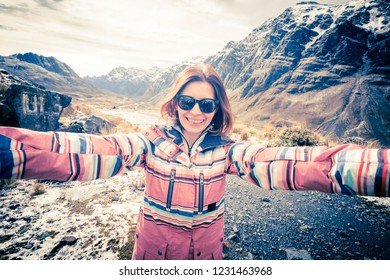 Happy smiling girl with black glasses taking selfie on the background of amazing rocky Andes