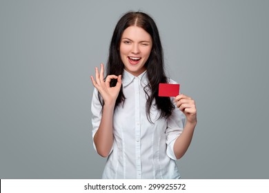 Happy smiling girl in casual clothing, showing blank credit card, on gray background