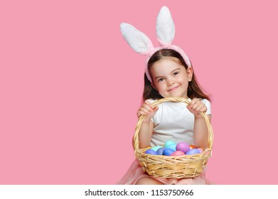 Happy smiling girl with Easter bunny  headband with  her basket with eggs