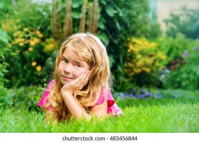 Happy smiling girl enjoys her summer holidays. Summer park. Happy childhood.