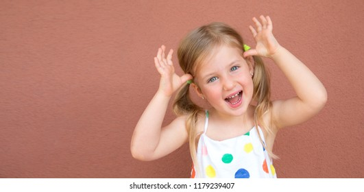 Happy smiling girl having fun over colorful red background. Education for preschool and kindergarten child.