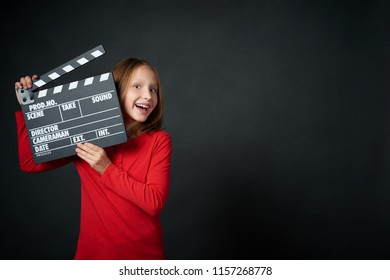 Happy smiling girl holding clap board, over dark background