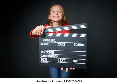 Happy smiling girl holding clap board, over dark background. Shallow depth of field, focus on clapper board