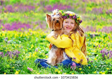 Happy smiling girl hugging her yorkshire terrier against flower meadow background