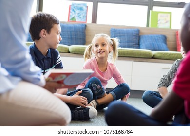 Happy smiling girl listening stories from book read by teacher at library. School children listening to fairy tale book in preschool read by woman at school. Cute girl with pigtails sitting on floor.