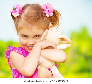 Happy smiling girl with lovely soft toy in the garden in daycare, having fun outdoors, spring season, happy childhood concept