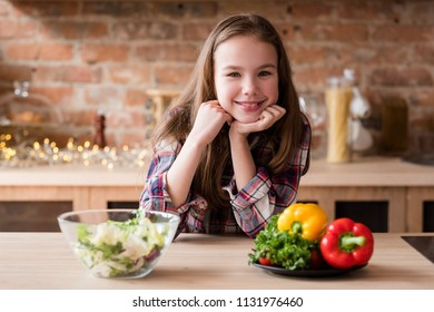 happy smiling girl loves veggies. healthy vegetable salad meal for wholesome child nutrition.