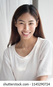 happy smiling girl; portrait of positive relaxed happy smiling asian woman smiles in indoor home environment; young adult asian persian woman or asian middle east woman model