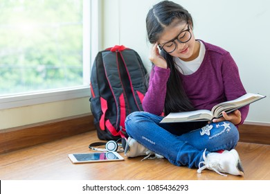 Happy smiling girl reading a book for exam at classroom corner,education and school concept.