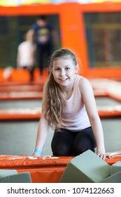 Happy and smiling girl resting while jumping trampolines