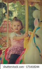Happy smiling girl riding on horse on carousel outdoors summer background. Vintage portrait