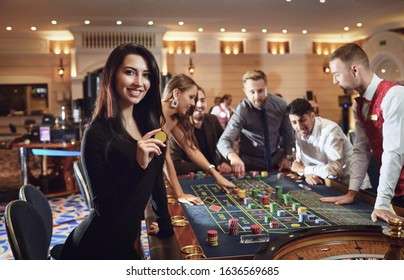 Happy smiling girl smiling at the roulette in a casino
