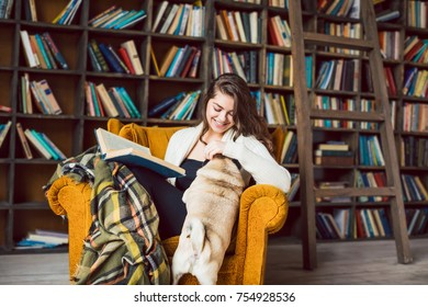 Happy smiling girl sitting on the chair in home library and playing with cute fat pug dog. Lovely lifestyle moment.