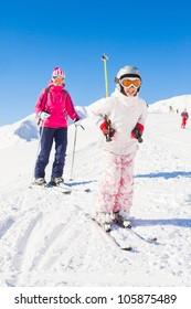 Happy smiling girl in ski goggles and a helmet with his mother, Zellertal, Austria. Vertical view