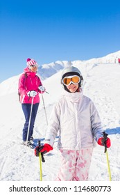 Happy smiling girl in ski goggles and with her mother, Zellertal, Austria