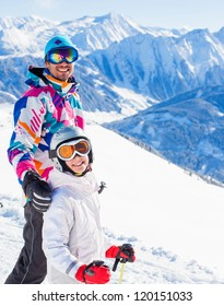 Happy smiling girl in ski goggles and with her father, Zellertal, Austria. Focus on the girl