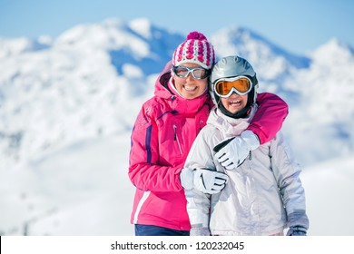 Happy smiling girl in ski goggles and with her mother, Zellertal, Austria. Focus on the girl