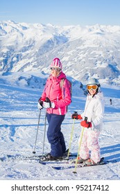 Happy smiling girl in ski goggles and a helmet with his mother, Zellertal, Austria