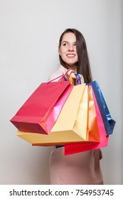 Happy smiling girl stands hoding shopping bags from black friday sale for holidays