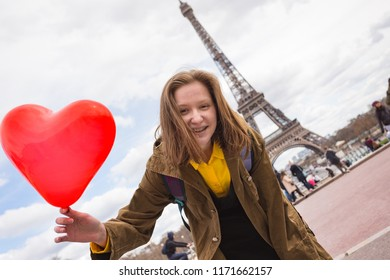 happy and smiling girl student with a balloon in the shape of a hearton the background of the Eiffel Tower in Paris. France