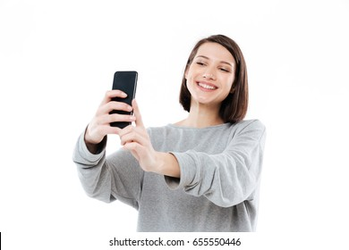 Happy smiling girl taking selfie on mobile phone isolated over white background