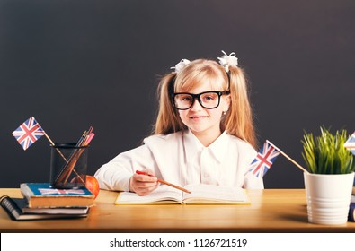 Happy smiling girl wears in smart eyeglasses learning English language with book before dark background