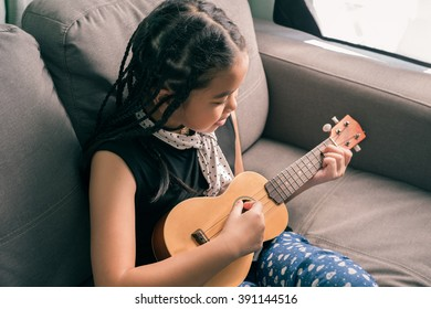 Happy smiling girl,dreadlocks hair style ,learning to play the Ukulele