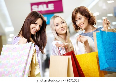 Happy smiling girls in shop with purchases