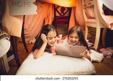 Happy smiling girls using digital tablet in house made of blankets
