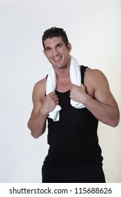 happy smiling good looking male bodybuilder just done a work out with a towel around his neck