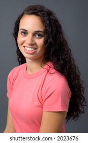 Happy, smiling green-eyed brunette woman with long hair, in salmon colored t-shirt on a neutral grey background.
