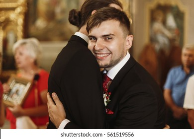 Happy, smiling groom hugging bestman after wedding ceremony in church, stylish handsome man embracing groomsman friend indoors and smiling