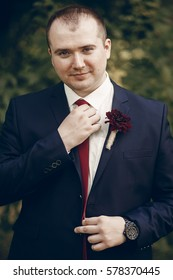 Happy, smiling groom in stylish suit with red boutonniere holding tie while posing outdoors, newlywed groom concept