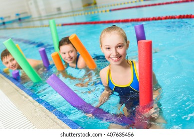 Happy and smiling group of children learning to swim with pool noodle