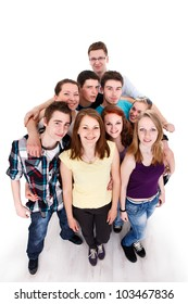 Happy smiling group of young friends standing and embracing together, top view