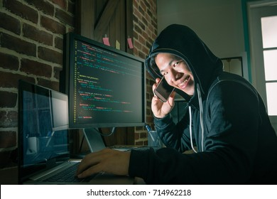 happy smiling hacker man using mobile smartphone doing telecommunications fraud and successfully blackmail many money feeling cheerful.