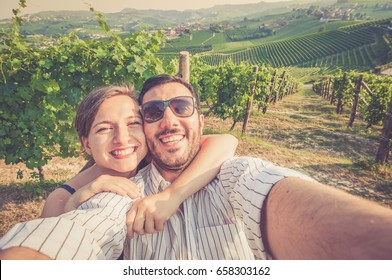 happy smiling handsome couple visiting vineyard area and taking photo selfie for wine tasting tour in Roero Monferrato Langhe Barolo town. vintage colors photo
