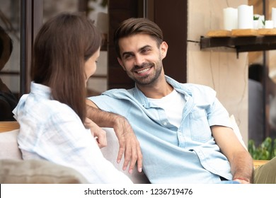 Happy smiling handsome man having good conversation with young woman, boyfriend looking at girlfriend, having fun together, first date concept, friends share thoughts, pleasant news in cafe