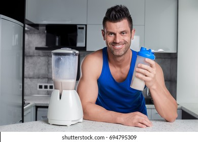Happy smiling handsome sporty looking man bodybuilder with strong muscles in blue tank top holding shaker with healthy milk protein cocktail mixed in blender in black and white high-tech style kitchen