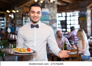 Happy smiling handsome waiter in a restaurant holding a tray with a salad and glasses full of wine in a restaurant