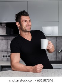 Happy smiling healthy sporty looking handsome charismatic man in black t-shirt outfit drinking tea or coffee or cacao or juice from nice ceramic cup in black and white modern style design kitchen