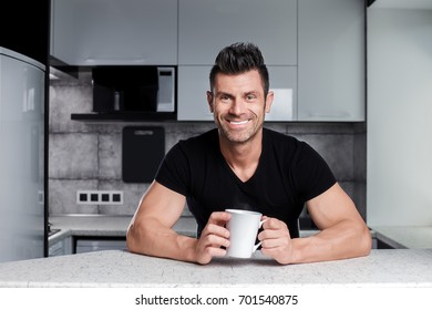 Happy smiling healthy sporty looking strong muscle handsome charismatic man in black t-shirt drinking tea or coffee or cacao or juice from nice white ceramic cup in hi-tech modern style design kitchen