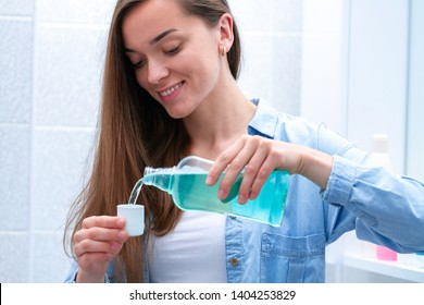Happy smiling healthy young woman using in bathroom a mouthwash gel to rinsing mouth, fresh breath, dental and gums health. Oral hygiene and teeth care